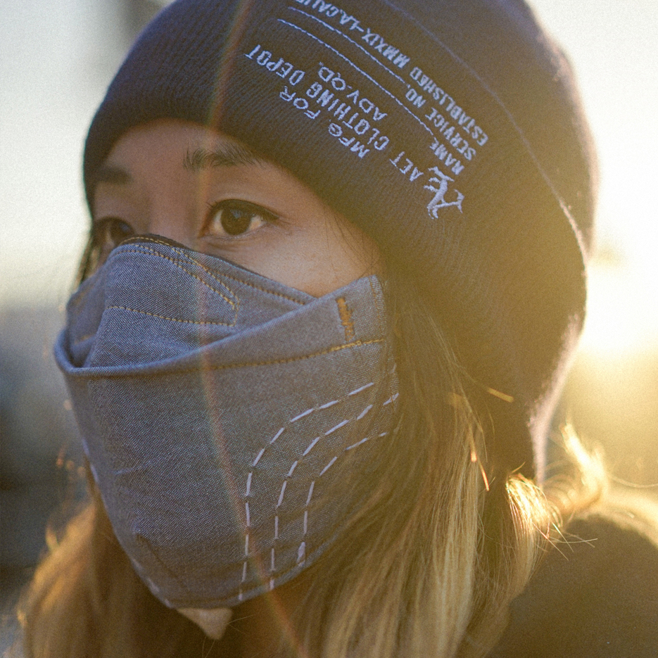 woman with beanie and custom face mask and bjj apparel. Sun flare effect. Golden hour in LA