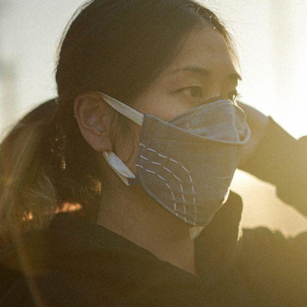 woman fixing her hair wearing custom face mask. soft LA sun light