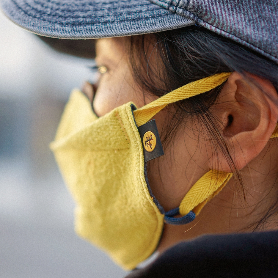 close up left side custom face mask on woman showing detail of AET tag