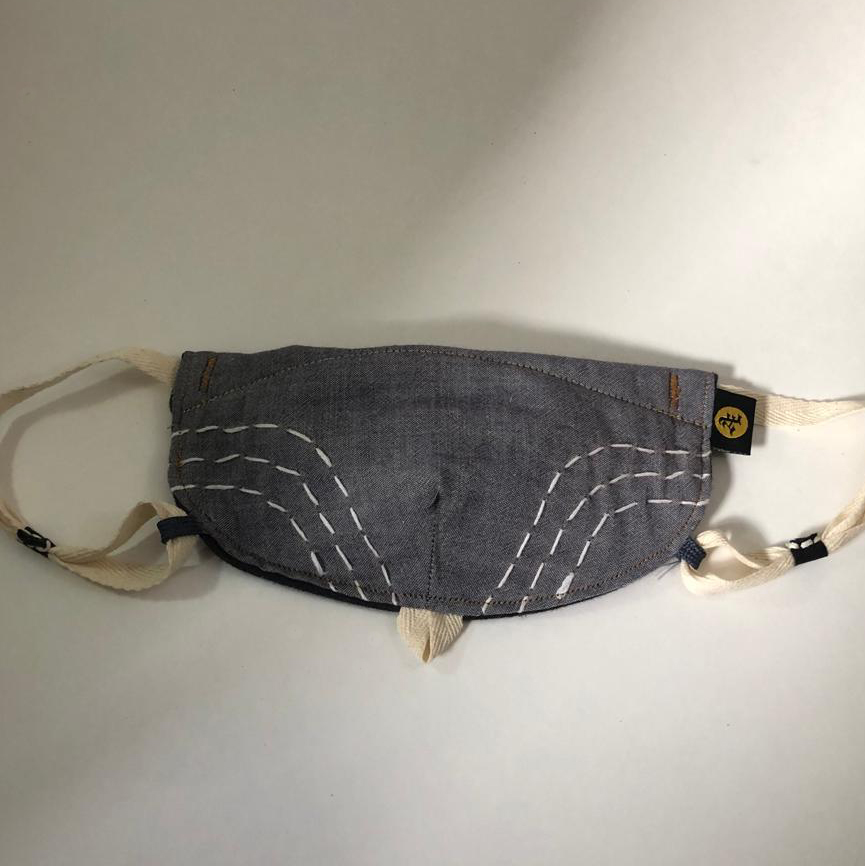Product shot of Boro custom face mask folded front view. this mask is a chambray denim like color with simple embroidery accents following cheek lines